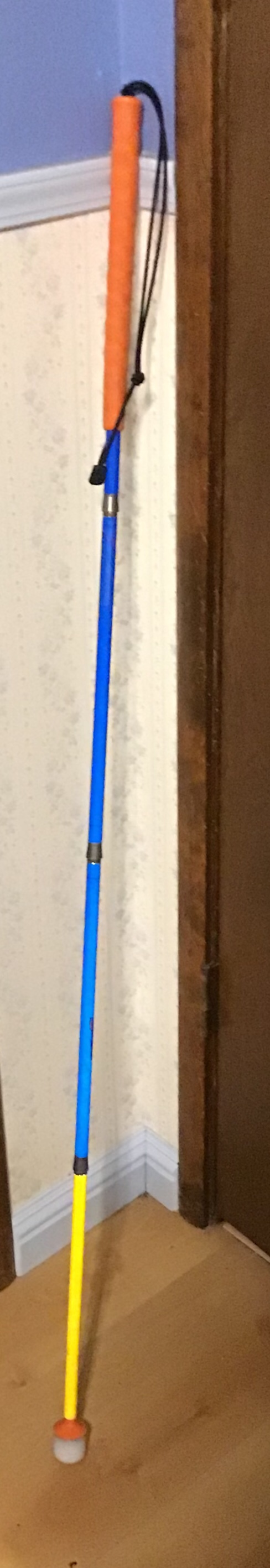 An orange, blue, and yellow cane leaning against a wall that is white on the bottom and blue on the top.