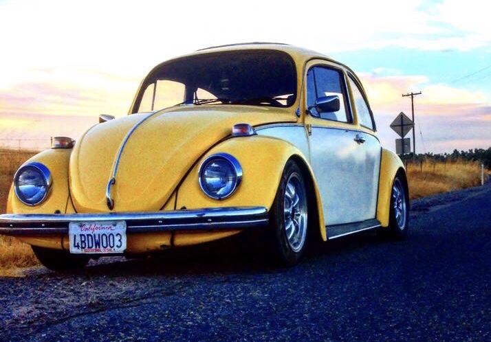 A yellow VW bug with white doorsparked on the road.