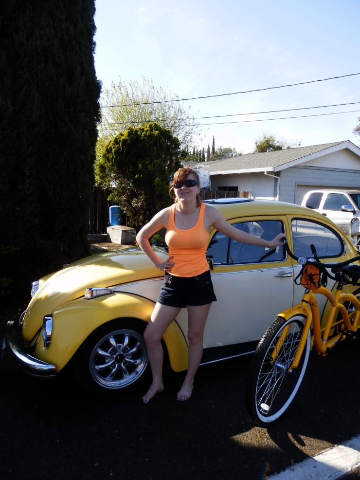 Image description: Chelsey standing infrunt of a yellow bug with a yellow tandem bicke nex to it.
